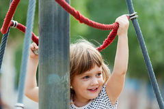 Baby girl climbing at ropes Stock Photo