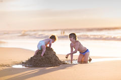 Baby girl climbing sand castle her brother was builded Stock Images