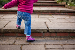 Baby girl climbing steps Royalty Free Stock Images