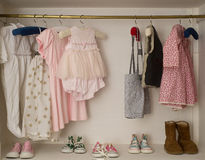 Baby Girl Closet with hanging dress & boots Royalty Free Stock Image