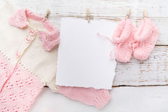 Baby girl clothes with blank card on white wooden background. Flat lay. Owerhad view Stock Photo