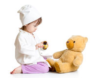 Baby girl with clothes of doctor spoon feeding ted Stock Image