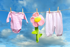 Baby girl clothes with flower  on the clothesline Royalty Free Stock Photos