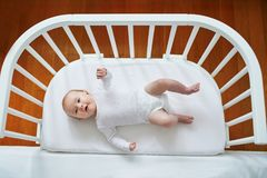 Baby girl in co-sleeper attached to parents` bed Royalty Free Stock Photo