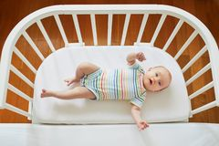 Baby girl in co-sleeper crib. Adorable baby girl in co-sleeper crib attached to parents ` bed. Little child having a day nap in cot. Infant kid in sunny nursery royalty free stock images