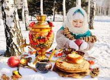 Baby girl in coat and headscarf in the Russian samovar in the ba Royalty Free Stock Photos