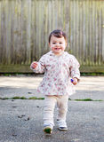 Baby girl in a coat running in the street with flower Royalty Free Stock Photography