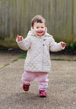 Baby girl in a coat running in the street Stock Photography
