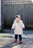 Baby girl in a coat running in the street smiling Royalty Free Stock Photography