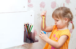 Baby girl with colored pencils Stock Images