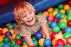 Baby girl and colourful balls. Baby girl playing in playground colourful ball pool Stock Photos