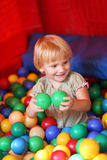 Baby girl and colourful balls. Baby girl playing in playground colourful ball pool Royalty Free Stock Image