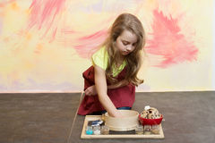 Baby girl cook with cookies. Sieve and ingredients for dough in chef apron on floor on abstract colorful wall. Cooking and baking concept. Child and childhood Royalty Free Stock Image