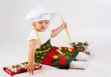 Baby girl in the cook hat Stock Photos