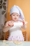 Baby girl in cook role on kitchen Royalty Free Stock Photos