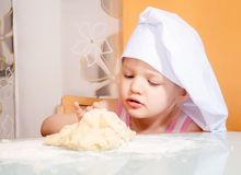 Baby girl in cook role molds from dough Stock Photography