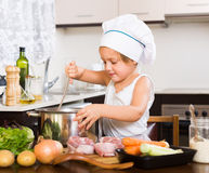 Baby girl cooking with meat Stock Photos