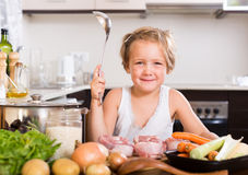 Baby girl cooking with meat Royalty Free Stock Photo