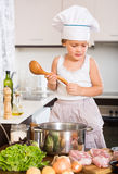 Baby girl cooking with meat Royalty Free Stock Images