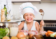 Baby girl cooking with meat Royalty Free Stock Image