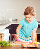 Baby girl cooking salmon Stock Photography