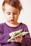 Baby girl counting money. Dollars. success, wealth management. Stock Images
