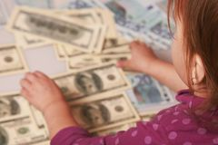 Baby girl counting money. Dollars. success, wealth management. Stock Image