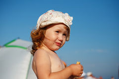 Baby girl covered in crumbs eats cookies on the beach Royalty Free Stock Image