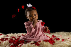 Baby girl covered with rose pedals Stock Photo
