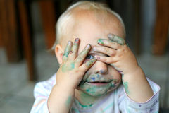 Baby Girl COvering Messy Face with Little Hands. A one year old baby girl is holding her paint covered hands over her messy face, and peeking out of her fingers royalty free stock image