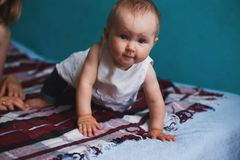 Baby girl crawling at bed in living room royalty free stock photo