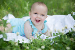 Baby girl crawling on the grass. Selective focus her eyes. Royalty Free Stock Images