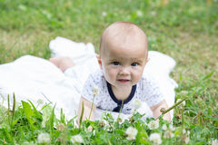 Baby girl crawling on the grass. Selective focus her eyes. Royalty Free Stock Photography