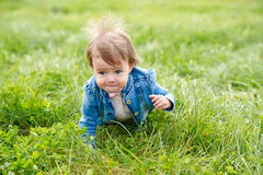 Baby girl crawling on the green grass Stock Images