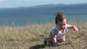 Baby girl crawling outdoors.