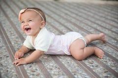 Baby girl crawling outside Stock Image