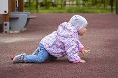 Baby girl crawling on the playground. A child in warm clothes on all fours. A 1 year old baby walks near the house in spring. Autumn clothes. Whole child royalty free stock photography