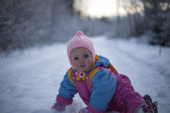 Baby Girl Crawling in Snow. Portrait of baby girl crawling on the snow-covered footpath Stock Photography
