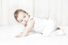 Baby girl crawls on a bed Royalty Free Stock Images