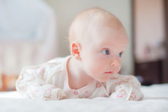 The baby girl crawls on the white bed Royalty Free Stock Image