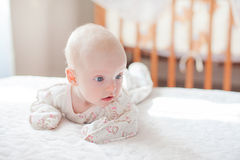 The baby girl crawls on the white bed Royalty Free Stock Images