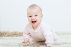 Baby girl creeping on the carpet. Happy little baby girl creeping on the carpet at home Royalty Free Stock Images