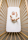 Baby girl in a crib. A small baby girl lying in a crib royalty free stock photos