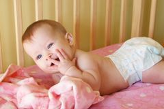 Baby Girl in Crib with hand to face Stock Photo