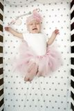 Baby girl cries in bed with a fluffy pink skirt. capricious child. crying baby top view royalty free stock photos