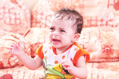 Baby girl cry. Ing on bench Stock Photos