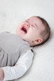 Baby girl crying over white bedcover Stock Photography
