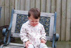 Baby girl crying sitting on a chair in the garden Royalty Free Stock Image