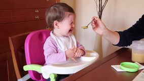 Baby girl crying with spoon food. Baby girl sitting on feeding chair crying with a spoon food stock video