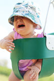 Baby Girl Crying in Toddler Swing. A baby girl is crying as she sits in a toddler swing at a playground at the park, on a summer day royalty free stock photo
